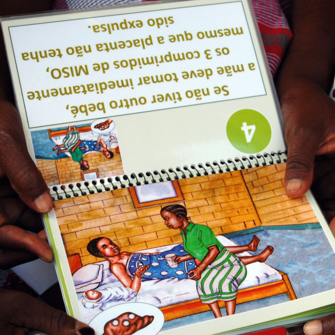 The birth attendants review a booklet on the use of misoprostol that has easy-to-understand illustrations.