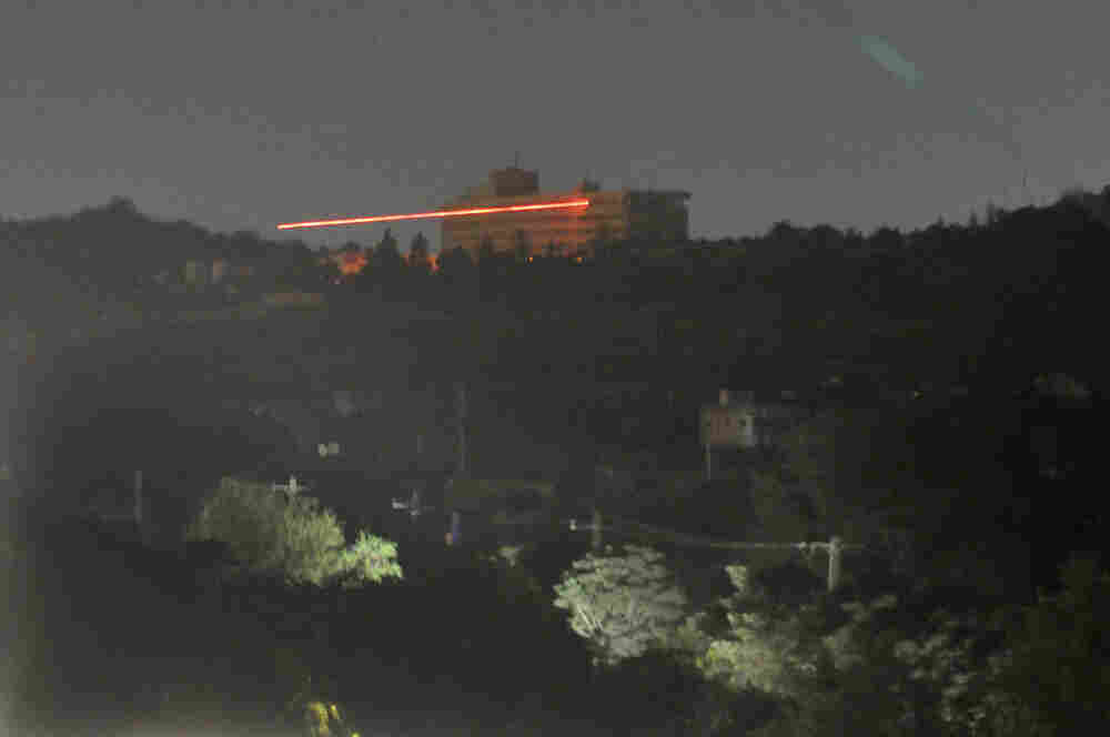 The Inter-Continental hotel in seen in the dark as tracer bullets are shot during an attack in Kabul.