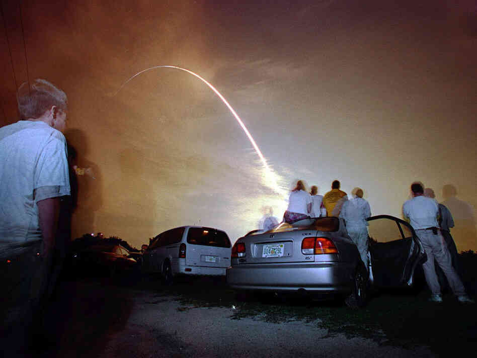 Onlookers crowd around their cars in the NASA causeway as they watch the  US Space Shuttle Atlantis blast off into orbit from launch pad 39-B at  Kennedy Space Center in the early morning hours of July 12 2001.