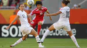 Lauren Cheney, left, and Carli Lloyd, right, of the U.S. battle for the ball with Yun Mi Jo of Korea DPR in their opening Group C match of the FIFA Women's World Cup at Rudolf-Harbig-Stadion in Dresden, Germany.