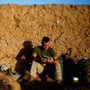 "Darryl St. George, a Navy corpsman with Weapons Company of the 2nd Battalion, 8th Marines out of Camp Lejeune, N.C., reads a book as the sun rises over a temporary base nicknamed ""Patrol Base Suc"" in Helmand province, southern Afghanistan."