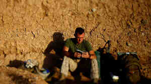 """Darryl St. George, a Navy corpsman with Weapons Company of the 2nd Battalion, 8th Marines out of Camp Lejeune, N.C., reads a book as the sun rises over a temporary base nicknamed """"Patrol Base Suc"""" in Helmand province, southern Afghanistan."""