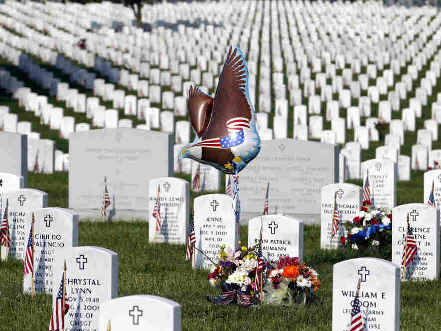 On Memorial Day, a patriotic balloon, flags and flowers adorned graves at Arlington National Cemetery.