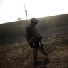 A Marine walks along a  mud wall while conducting a search and clearing operation in Afghanistan's Helmand province, as the dust from a wheat thrashing machine falls like snow.