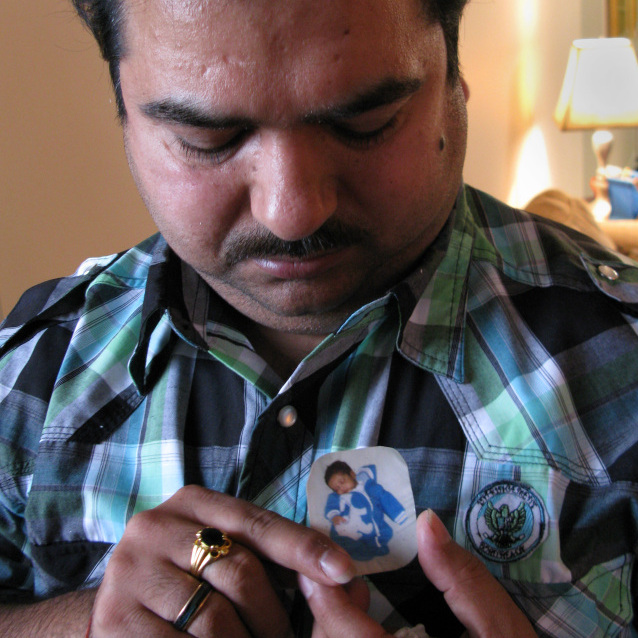 Dinesh Kumar looks down at a portrait of his son, who died when he was 5 weeks old.