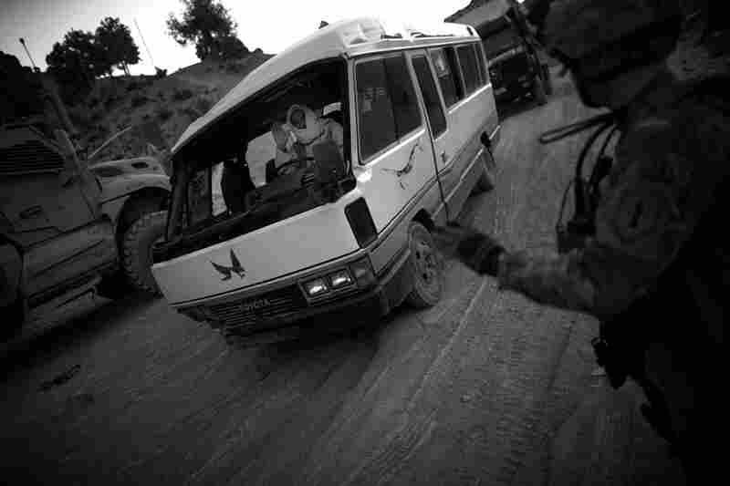 A soldier with Butcher Troop waves to a driver who rolled his bus earlier in the day on the dangerous switchbacks section of the Khost-Gardez highway in Paktia province.