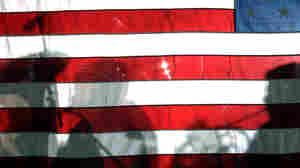 BOSTON, MA - SEPTEMBER 14:  Shadows of musicians from the Boston Symphony Orchestra fall on the American flag during a performance.