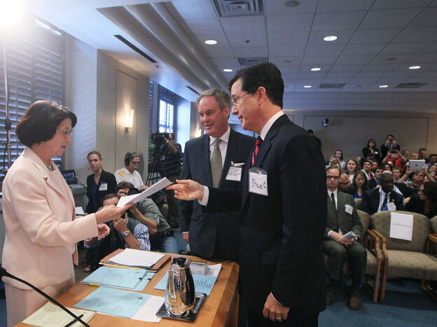 Comedian Stephen Colbert with his attorney, Trevor Potter, turns in a document at a Federal Election Commission hearing, June 30, 2011.