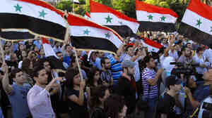 Syrians carry national flags during a candlelight vigil in honor of those who were killed in recent violence, in Damascus on Wednesday. It was the first officiall