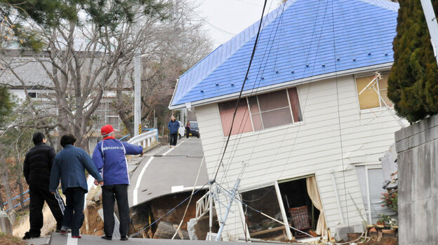 Residents check an earthquake-damaged house in Sukagawa city on March 11, in the Fukushima prefecture in Japan. A researcher says that after large-scale natural disasters, it's frequently friends and neighbors who are key to survival.