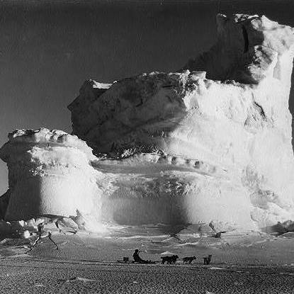 A member of the Terra Nova Expedition (or British Antarctic Exploration team) travels by dogsled in front of a weathered iceberg, circa 1910 or 1911.