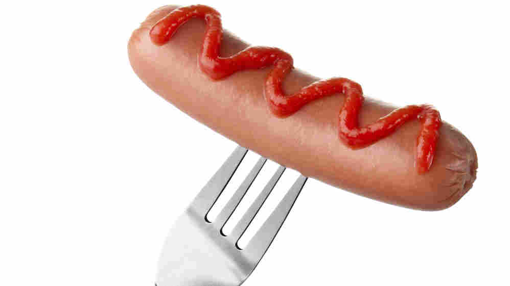 Hot dog on fork with ketchup topping.