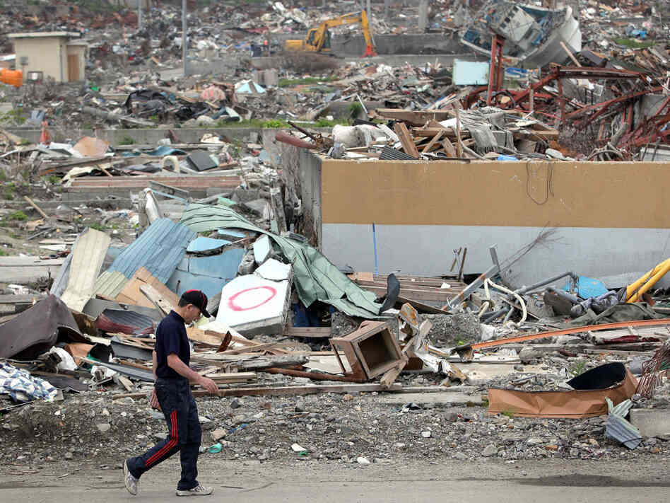 A man walks past the debris on June 12, 2011 in Otsuchi, Iwate, Japan. Japanese government has been struggling to deal with the earthquake and tsunami as well as the troubled Fukushima Daiichi Nuclear Power Plant. The fear of infectious disease outbreak  is mounting due to the humid rainy season and delay of the debris clearing.
