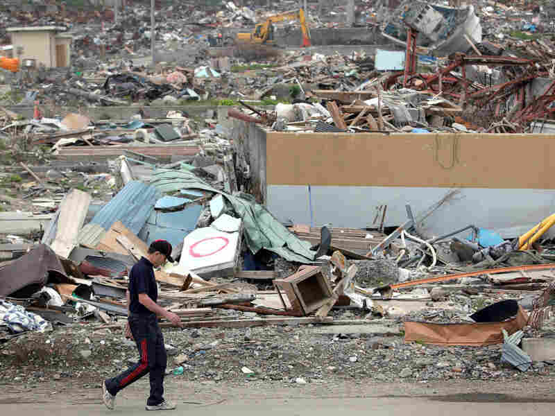 A man walks past the debris on June 12, 2011 in Otsuchi, Iwate, Japan. Japanese government has been struggling to deal with the earthqu