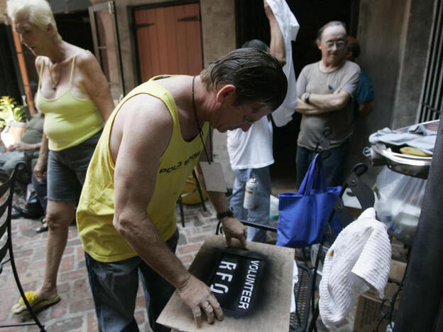 Residents of the Faubourg Marigny neighborhood of New Orleans printed T-shirts during a community meeting on Sept. 9, 2005. The neighborhood organized a cleanup effort even as mandatory evacuation of the city was under way. Refusing to obey the order to evacuate, many residents remained in their houses.