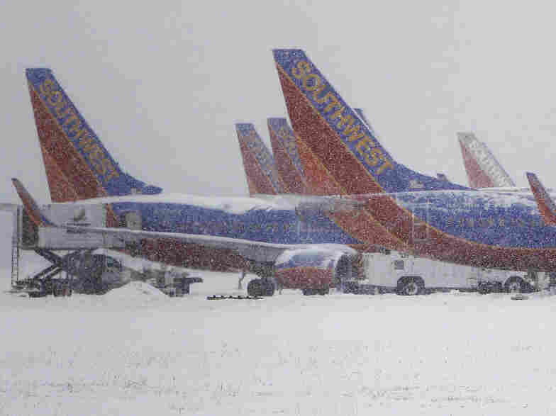 Southwest Airlines planes sit idle at Love Field in Dallas as snow continues to fall on Feb. 4. A study finds that airplanes flying through certain types of clouds can actually cause snowfall. Wingtips and propellers create ice crystals, which later fall to earth.