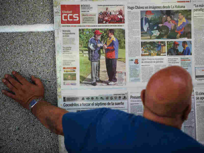 A man reads about Venezuelan President Hugo Chavez' meeting with Fidel Castro on a newspaper glued to a wall in Caracas,on June 29, 2011. Amid suspicion that Chavez is seriously ill, the president canceled an upcoming summit.
