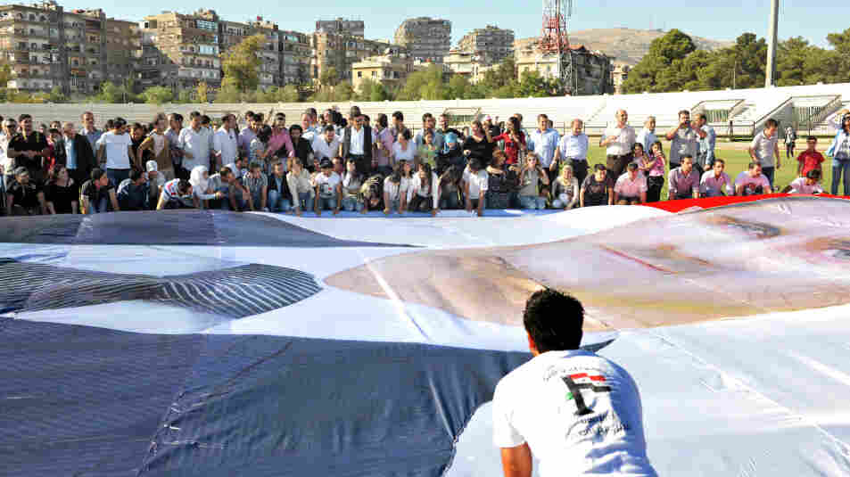 Regime supporters prepare to mount a huge poster of Syrian President Bashar al-Assad at Al-Jalaa Stadium in Damascus.