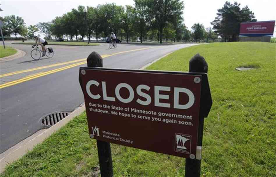 A bicyclist rides on the road leading out of the closed Fort Snelling historic site Friday in Minneapolis, after negotiations over the state budget broke down and the government shut down at midnight.