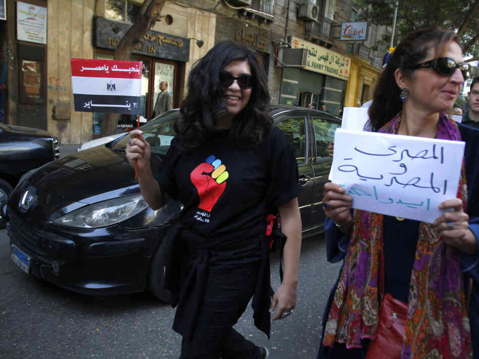 "An Egyptian woman carries a banner that reads ""Egyptian man and woman in one hand,"" on a march to Cairo's Tahrir Square to celebrate International Women's Day. The protest demanding equal rights and an end to sexual harassment turned violent when men verbally abused and shoved demonstrators, telling them they belong at home."
