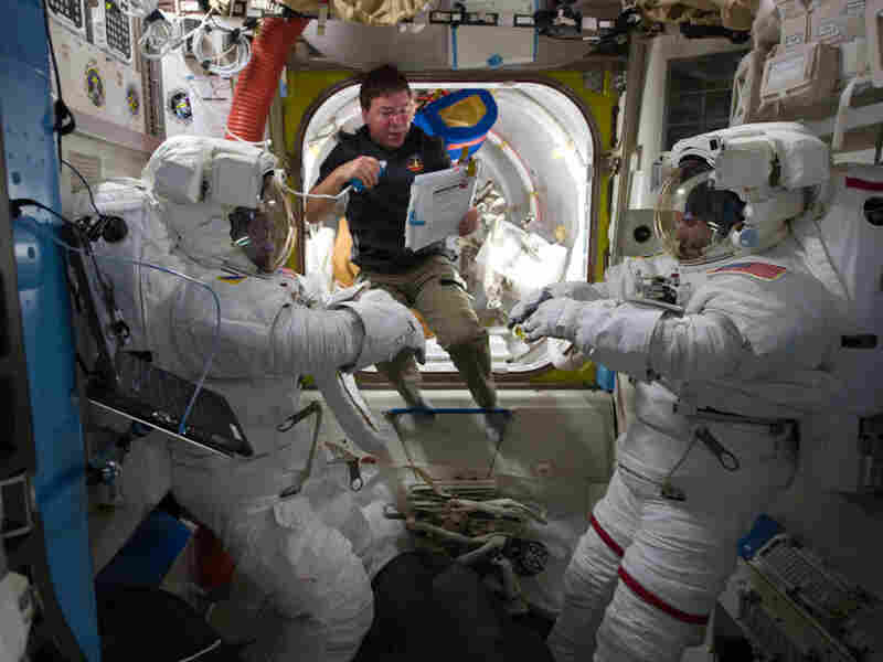 Mission Specialist Michael Barratt prepares his fellow astronauts for a spacewalk in the airlock of the International Space Station in February 2011.