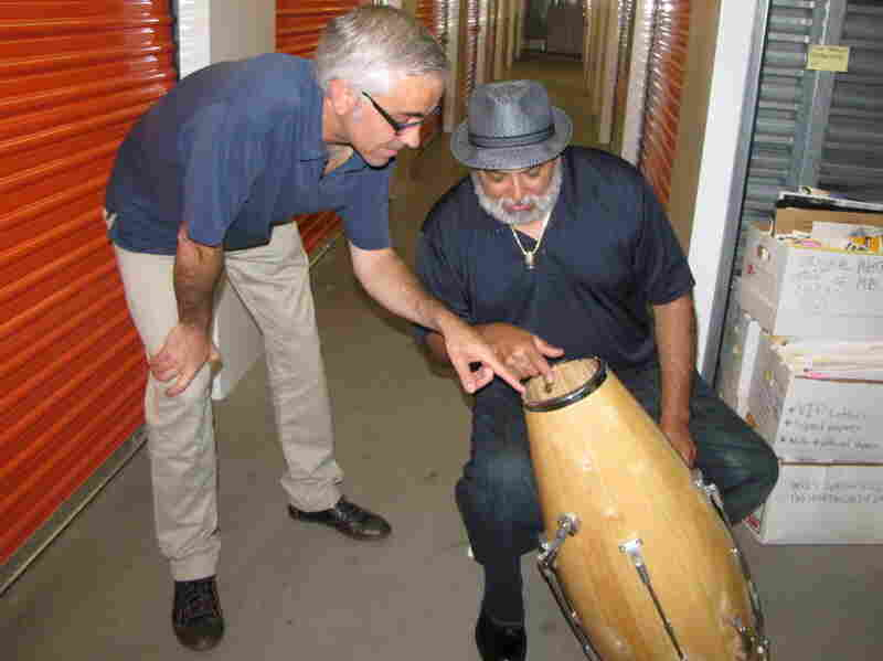 Attorney Kevin Costanza and drummer Poncho Sanchez examine one of Brando's patented conga-tuning devices.