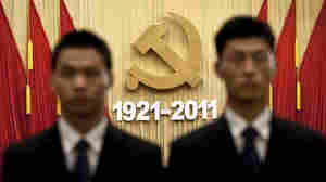 Chinese security officers stand in front of the Communist Party's emblem while singing a patriotic song during the celebration of the party's 90th anniversary Friday at the Great Hall of the People in Beijing. President Hu Jintao said the party's ability to adapt made China affluent and powerful and that the party must fight corruption to retain public support and continue its uncontested rule.