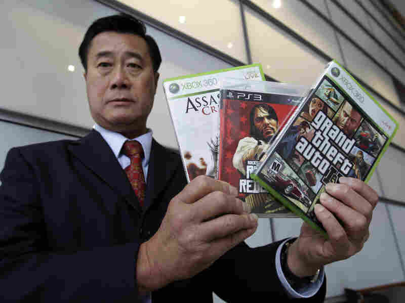 """Calif. State Sen. Leland Yee, D-San Francisco, holds up three video games after a news conference in San Francisco, Monday. The Supreme Court ruled that it is unconstitutional to bar children from buying violent video games, saying government doesn't have the authority to """"restrict the ideas to which children may be exposed"""" despite complaints."""