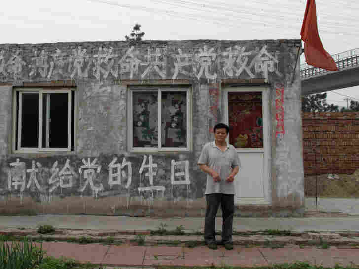 """Thirty-year Communist Party veteran Wang Jiang stands in front of his building, painted  with the words, """"Save me, CCP!"""" He says his house was illegally demolished,  and he's now seeking justice rather than compensation. His aim is to shame the  Communist party into helping him."""