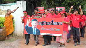 """A Buddhist monk sprinkles holy water on Red Shirt leaders  as they parade through Baan Suksomboon in northeastern Thailand's Udon  Thani province. Baan Suksomboon is  Thailand's 255th  Red Village to declare its support for  opposition candidate Yingluck Shinawatra. Thaksin Shinawatra, pictured on the  campaign poster, jokingly calls his sister his """"clone."""""""