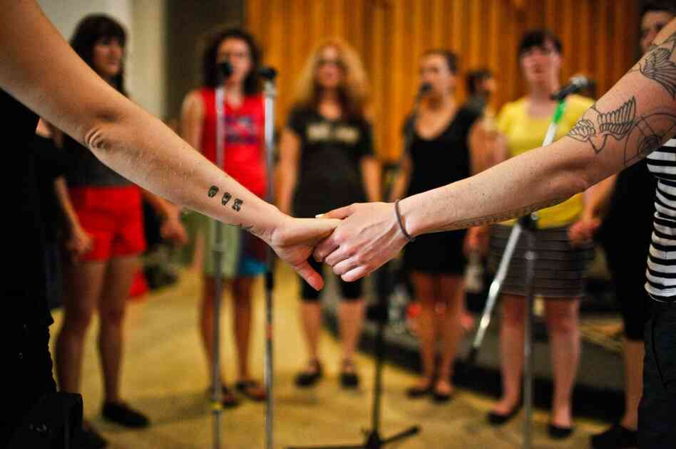 Singers from the Assembly of Light Choir hold hands as they prepare for their performance later that evening.