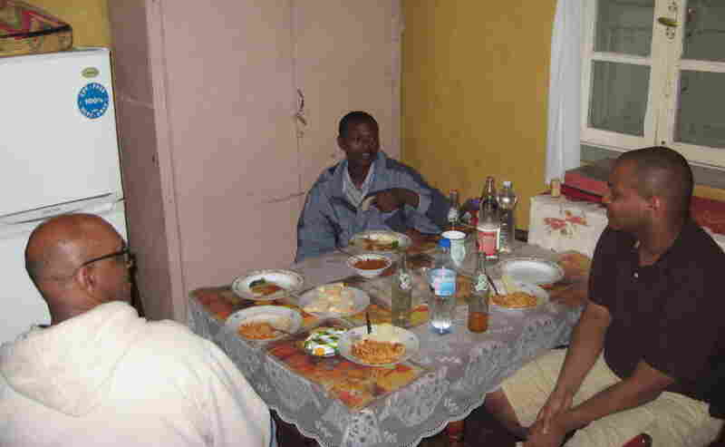 Tinbete Ermyas (center) sits down to eat with his uncle and father in Ethiopia.