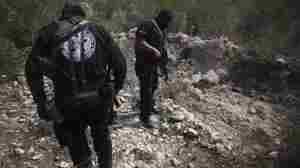 Police officers stand next to a hole they say was used as a mass grave near San Fernando in the Mexican state of Tamaulipas in late April. Almost 200 bodies were found that month in Tamaulipas. Prosecutors believe the killings were carried out by members of the Zetas drug cartel.