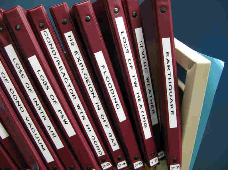 A shelf in the control room simulator holds binders of protocols for how to handle emergency situations.