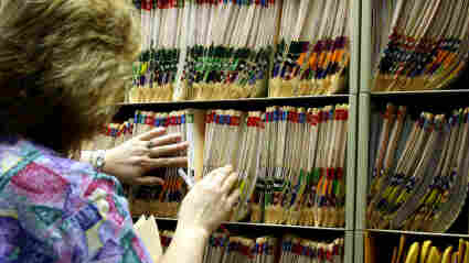 A nurse looks for medical records.