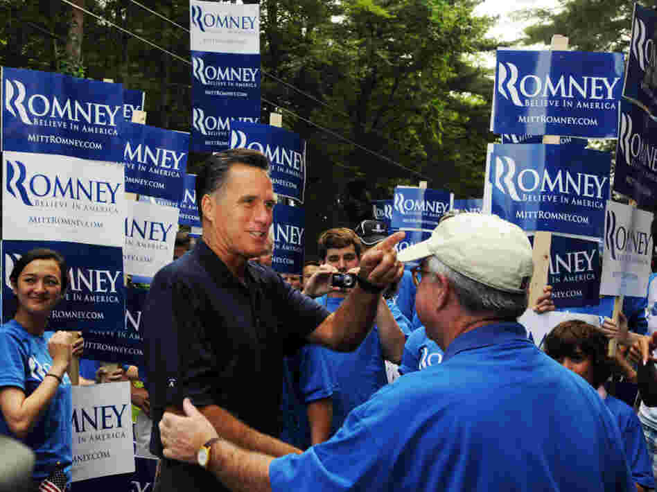 Former Massachusetts Gov. Mitt Romney shakes hands while marching in the Fourth of July parade in Amherst, N.H.