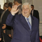 Syrian Foreign Minister Walid Moallem waves to reporters before a meeting with his counterpart from Iraq, in Baghdad on May 31, 2011.