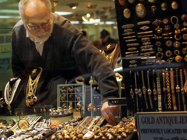 A gold jeweler reaches for a display piece at a shop in New York City in April. The price of gold in the international market is steadily rising. It's currently selling for about $1,500 an ounce