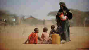 Sarura Ali (right) covered her eyes from wind-blown dust as she stood with her six children outside a food distribution point in the Dadaab refugee camp in northeastern Kenya on Tuesday (July 5, 2011). Sarura, her husband and their children trekked for eight days from their home in Sakow, Somalia. War and drought are forcing many Somalis to take desperate measures.