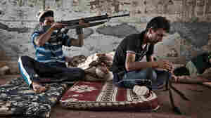 Libyan clean their weapons under a bridge near Bir Ayyad, a town approximately 25 miles from Zintan in the western mountains of Libya, on June 26.