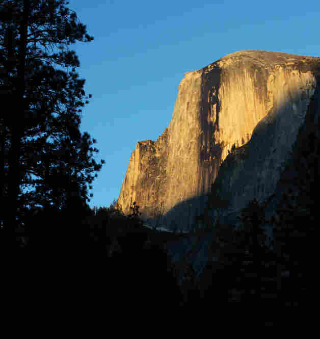 The last splash of sunlight fades away from the face of Half Dome, as seen from the Pines Campgrounds in Yosemite Valley.