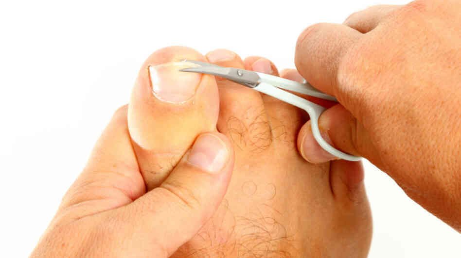 A man cutting his toenails.