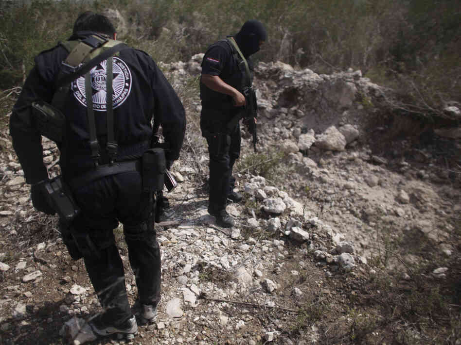 Police officers stand next to a hole that they say is used as a mass grave, near San Fernando, Tamaulipas state, Mexico in April. Security forces have unearthed many bodies in Tamaulipas where a drug gang is believed to be kidnapping passengers from buses and hiding their victims in secret graves, authorities said Tuesday.
