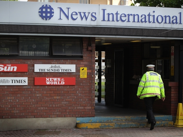 A policeman walks through the security gates at News International's Wapping plant on July 7, 2011 in London,  England.