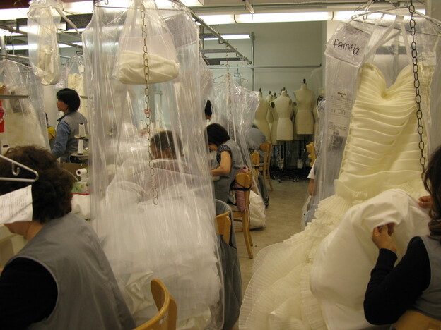 Seamstresses sew wedding dresses at Kleinfeld Bridal, one of the world's largest bridal emporiums. Brides who call because of the new law probably won't  have an appointment for another month.