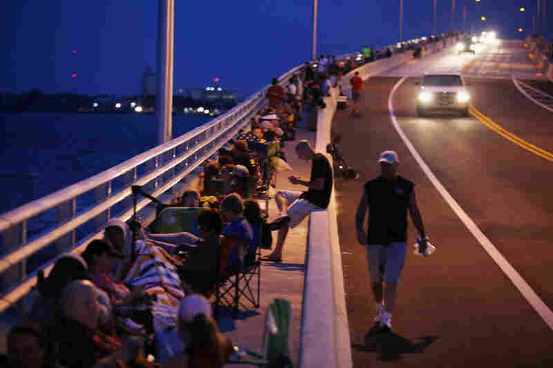 People line a bridge in Titusville, Fla., early Friday morning, making use of a different vantage point on the launch.