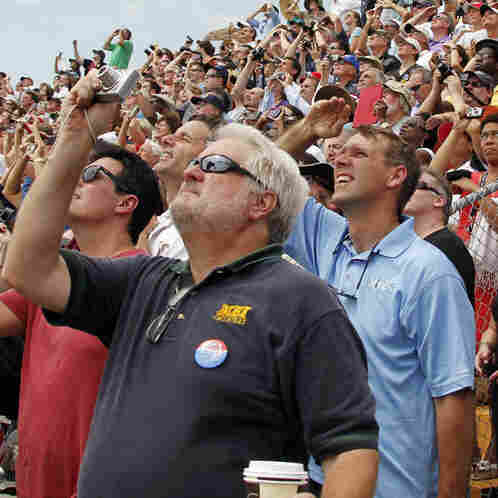 Spectators watch the space shuttle Atlantis lift off from the Kennedy Space Center Friday in Cape Canaveral, Fla. Atlantis is the 135th and final shuttle launch for NASA.