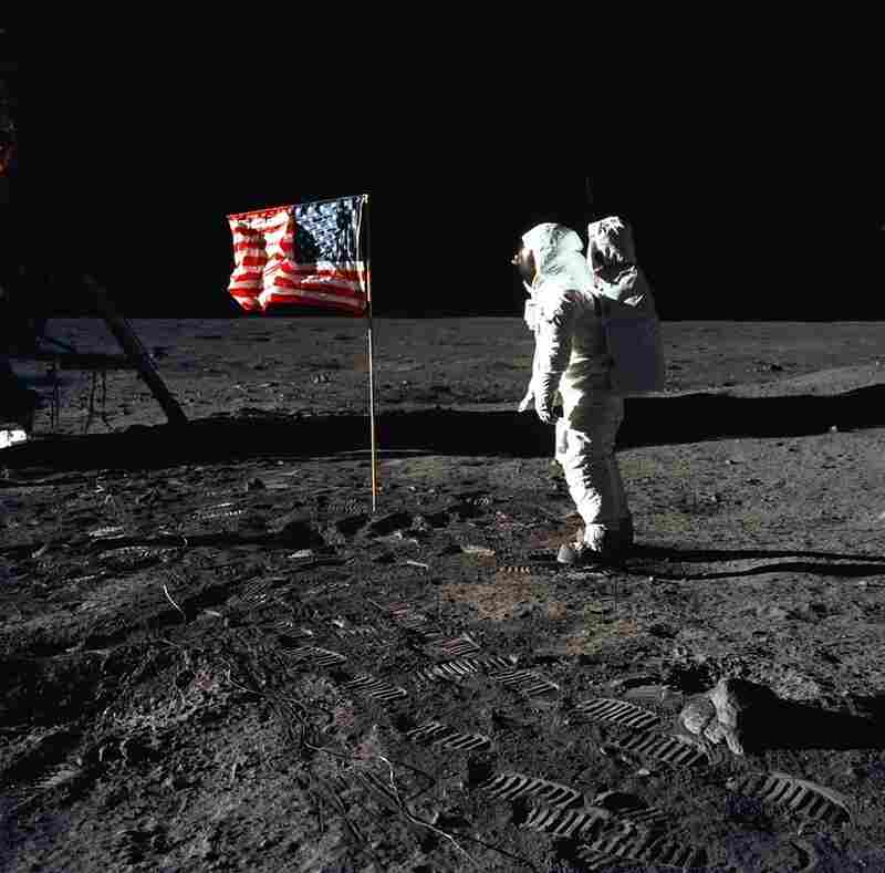 Astronaut Edwin (Buzz) E. Aldrin Jr., pilot of the Apollo 11 mission, poses beside a flag on the surface of the moon. One space policy analyst says the space shuttle program was the natural successor to the Mercury, Gemini and Apollo programs and evolved humans' ability to live and work in space.