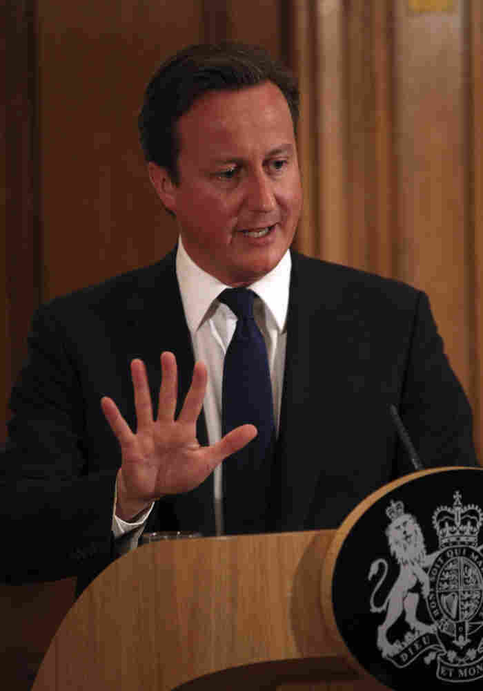 Britain's Prime Minister David Cameron promises a full investigation into the phone hacking and police bribery scandal that led to the collapse of the News of the World tabloid, at a press conference in London on Friday.