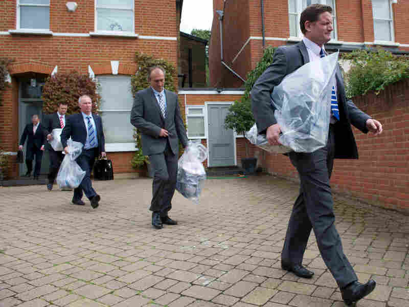 Investigators carry bags of evidence from the home of Andy Coulson, a former News of the World editor and Cameron aide, in London on Friday. Police arrested Coulson in the phone hacking scandal.